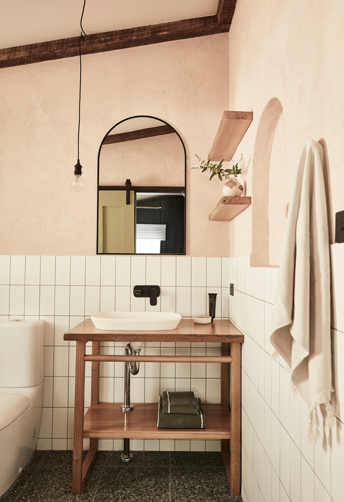 """With a beautiful bathroom integral to luxe holiday getaways, Saul splurged on stunning green terrazzo floor tiles from Tiles by Kate, which lay the foundation for the memorable space. White subway wall tiles are juxtaposed with an earthy pink Venetian render, and organic curves evoke a feminine feel, as do clay coloured Saardé towels and a pretty Life Interiors vessel displayed on a timber shelf. To complement the petite space, Saul designed and made the simple timber vanity, offset with a sleek matt black 'Contura' mixer tap and 'Contura 530' solid surface inset basin, both from [Caroma](https://www.caroma.com.au/
