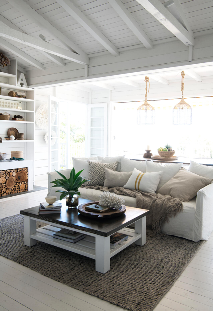 """Anchored by a Lifestyle Collective sofa adorned with a Beachwood chunky European linen throw and cushions including, second from left, the Walter G 'Swazi Mud', Coastal Drift 'Zimbabwe Block White' and Eadie Lifestyle 'Simpatico' in Mustard, the light-filled living space brims with cross-cultural mementos. Atop a Beachwood [coffee table](https://www.homestolove.com.au/10-of-the-best-coffee-tables-13248 target=""""_blank""""), a traditional parat (plate) and a coral, both from Home With Grace, draw the eye, while the tones of a rug from Home On Darley call to mind driftwood and a stormy sea."""