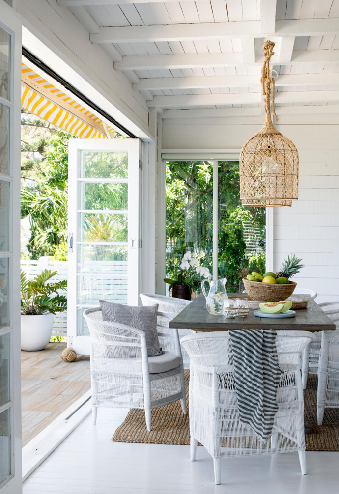 Pendant lights from Home With Grace spotlight a glorious place to dine, flowing out from the living room. Malawi Cane Traditional single chairs and seat pads in White set the scene for a long lunch, while pieces from Coastal Drift (the 'Ilala' woven mirror tray and 'Buhera' bowl) enhance the vista's raw appeal. The previous owners' use of a yellow-and-white awning inspired Monique to introduce yellow as a motif inside and outside the family home.