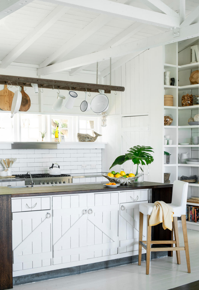 """Custom-made doors (with hardware from Hepburn Hardware) are a focal point of the kitchen island (above, by an Ikea stool) and conceal a surprise. """"Our TV's in there,"""" says Monique with a laugh. The island benchtop (left, showcasing crockery from Mud Australia) is restored Tasmanian oak with a dark stain treatment. """"There are always neighbours popping over, or people visiting from the east, or people coming for weekends,"""" says Monique who, along with Andrea, regularly entertains.Nonetheless, the kitchen's six-burner Ilve oven has been getting a rest lately. """"We always used to be a big 'roasts' sort of family, and now everything's pizza!"""" explains Monique, whose Mediterranean courtyard features a popular pizza oven."""