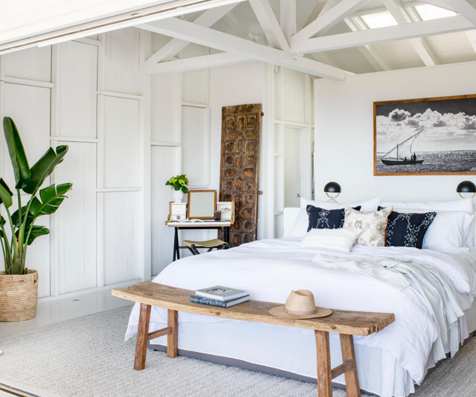"""A bench from Home With Grace echoes the natural tones in a Coastal Drift planter basket and keeps essentials within reach, while a striking pair of old African doors bookend the room. """"They've lived different lives for different purposes,"""" says Monique. """"Here, they're parted as if they're the doors into the ensuite bathroom."""""""