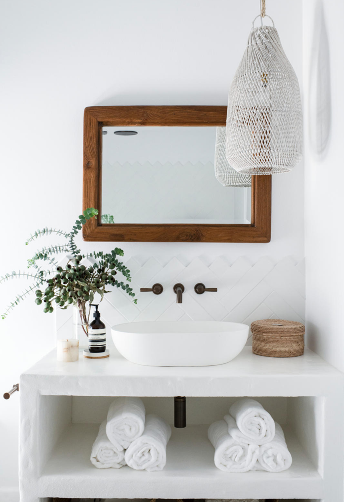 """""""We jackhammered three layers of tiles away from the floor in here,"""" recalls Monique, who designed the stunning concrete vanity, which has Brodware tapware in Weathered Brass Organic and a Nero Stone sink accessorised with Coastal Drift's 'Tiffin' basket, against a Beaumont Tiles splashback. A pendant by Home With Grace completes the starkly beautiful space."""