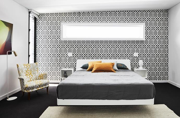 The main bedroom features a floating bed from Fanuli, Kelly Wearstler 'Imperial Trellis' wallpaper from Schumacher and charcoal carpet. Bedlinen, Ondene. Rug, Cadrys. Floor lamp, Fred International. Spectrum Figure 8 artwork by John Young.
