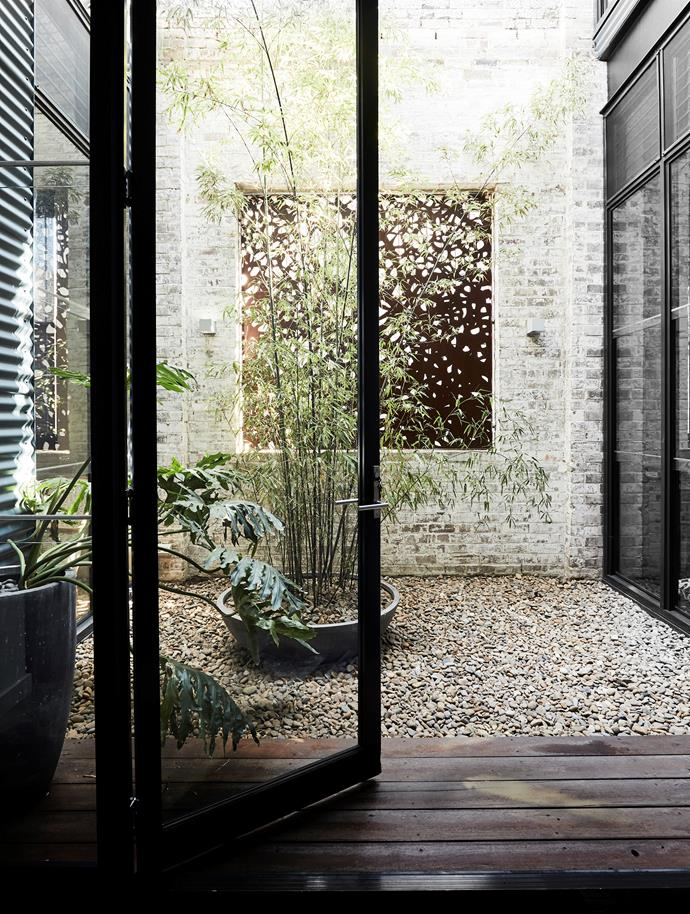 The courtyard fills a central void that funnels light into all three floors of the home. The feature screen is a custom piece by Lump Sculpture Studio.