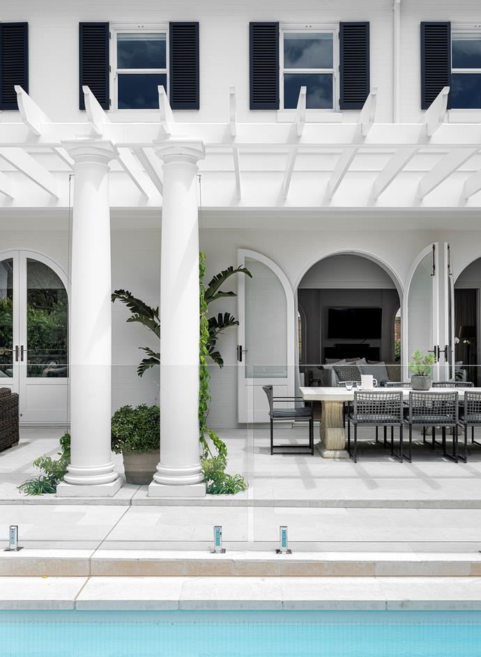 Classic details include arched doorways and columns. Exterior is painted in Dulux 'Natural White' with shutters in Dulux 'Black Caviar'. Pool tiles are Italian white glass mosaics from Marble & Ceramic