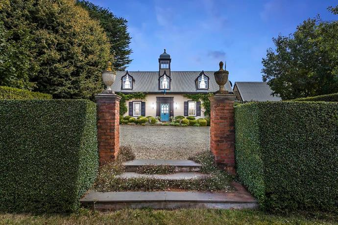The entrance to the property is flanked by expertly manicured hedges.