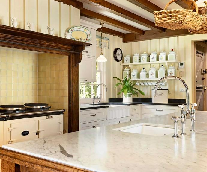 The kitchen features a marble island bench and a wood-burning AGA stove.