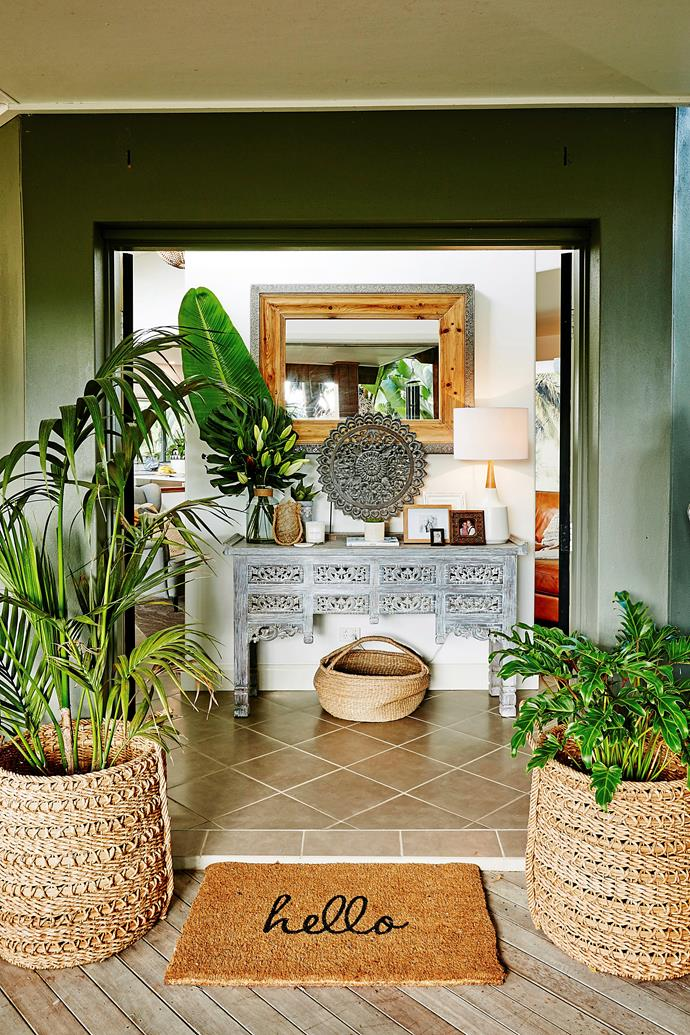 A mix of exotic or tribal homewares like the hand-carved round decorative piece, picture frames, table lamp and a scented candle add to the Balinese-style entryway.