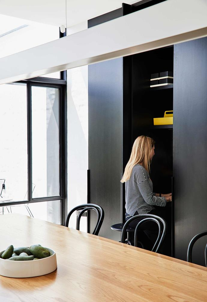 **Open-plan** Sunlight pours through a wall of floor-to-ceiling glass in the combined kitchen/dining room of this Melbourne home, where eating is far from the only thing that happens. The joinery running along one side of the home opens here to a cleverly concealed study nook, which maximises space without compromising the room's streamlined aesthetic.