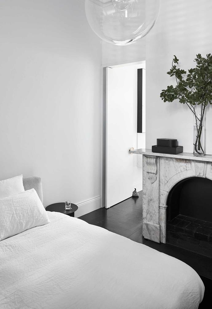 """**Main bedroom** A black Japan finish on the pre-existing floorboards has given this downstairs room a more contemporary look. Original Carrara marble mantel. Selene pendant, [Anibou](https://anibou.com.au/