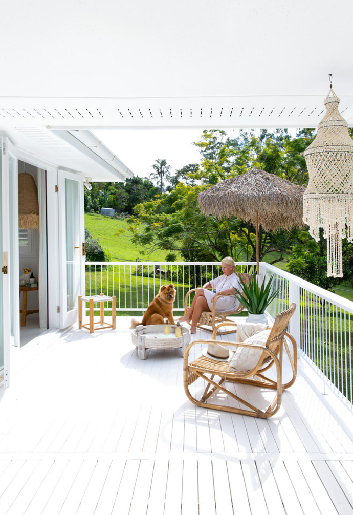 """Andy and adorable chow-chow Ginger Rose make the most of the deck, which was extended to run the full length of the house. Carefully selected cane chairs, plus a rustic bamboo umbrella from Ha'veli, create a relaxed resort vibe. """"I've always wanted one,"""" explains Andy of the brolly. """"The shape and hairy fronds remind me of the children's storybook character Grugg."""""""