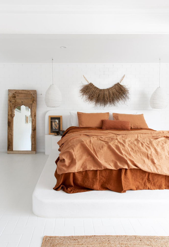 The perfect foil for the home's white-on-white palette is a splash of rich colour. In harmony with Andy's love of natural tones and materials, French linen in Ochre and Sandalwood from I Love Linen defines the guest bed, which sits upon a custom rendered concrete platform. A Woven Husk wall hanging and a timber-framed mirror from Alabaster Trader add texture.