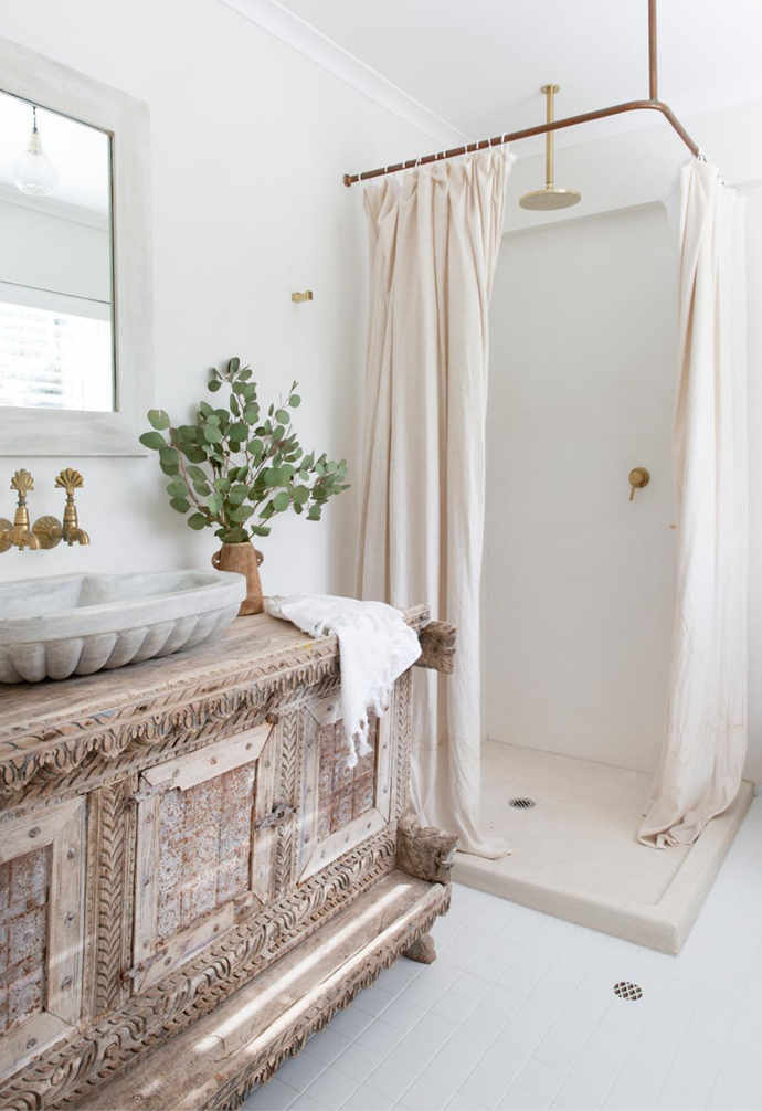 A charming curtain covers the shower in the main bathroom.