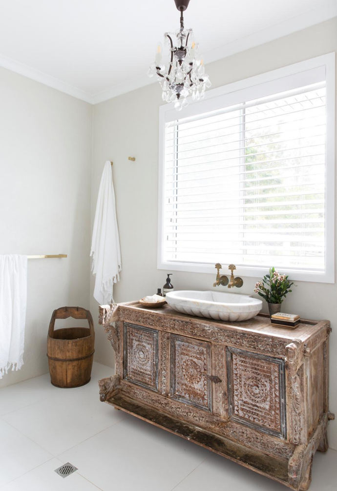 A hint of glamour is introduced in the bathroom with a chandelier above a vintage trunk turned vanity.