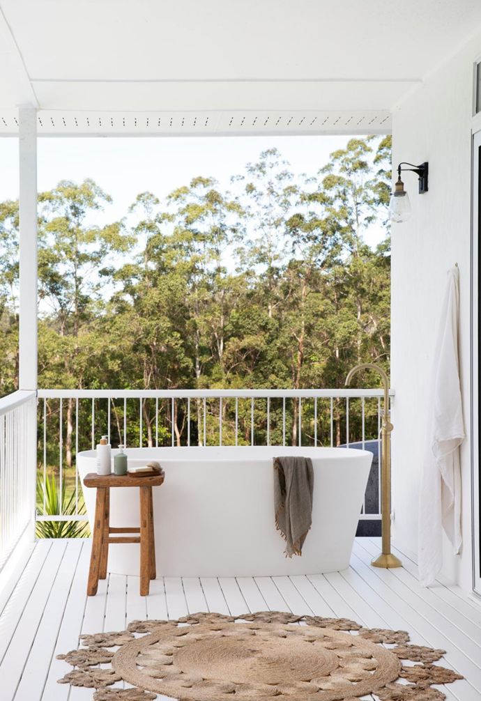 """A private bathtub on the back deck overlooking a sea of trees is the epitome of tranquillity. For a spa-like feel, the freestanding tub from Highgrove Bathrooms is teamed with brushed gold tapware from NCP, with a rustic timber stool handy for holding soaps. """"We took out the original bathtub from the main bathroom to create space, but because Izzy still loves to have a bath we thought it would be fun to try something outside,"""" says Andy. A 'Marigold' rug from Armadillo & Co completes the idyllic set-up."""