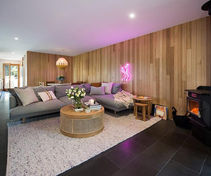 A panelled timber wall lends warmth to the open plan living room.