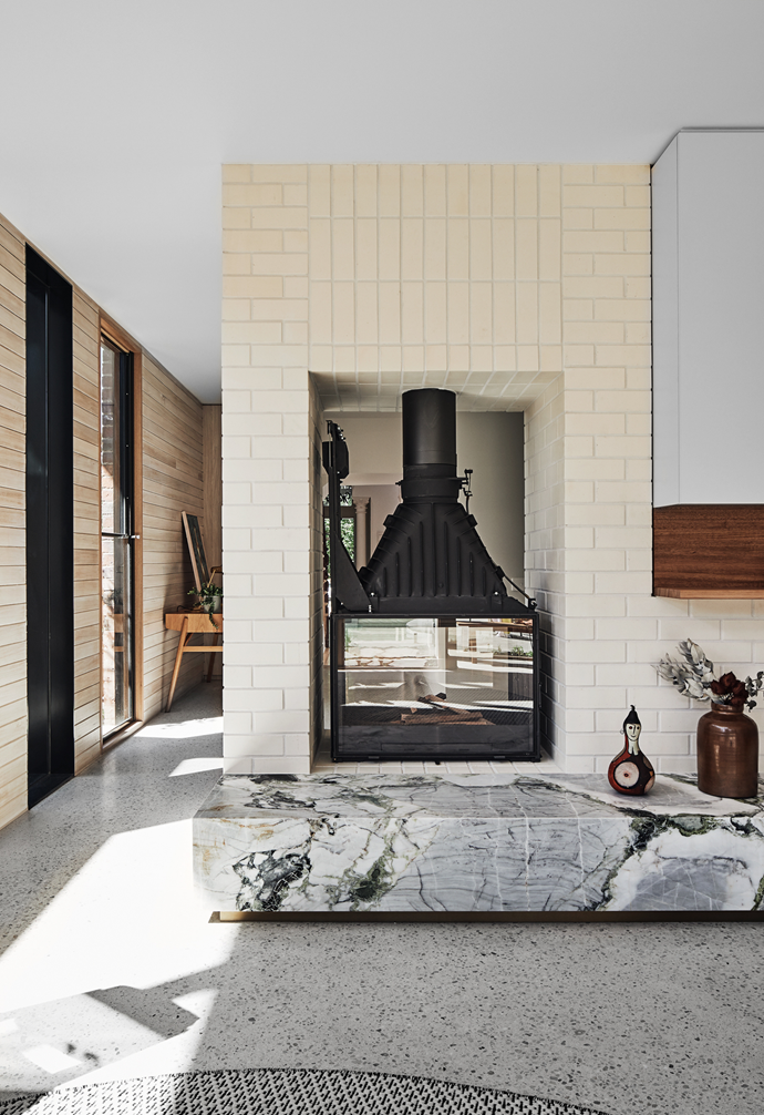 """The statement double-sided fireplace in the living room of this [sun-filled terrace](https://www.homestolove.com.au/modern-terrace-extension-melbourne-22221