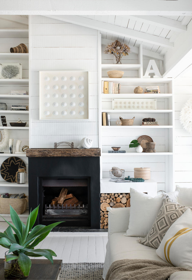 """Custom floating bookshelves with weatherboard panels create an effortless beachy look in the living room of this [light and bright coastal home](https://www.homestolove.com.au/mediterranean-style-home-sydney-22401