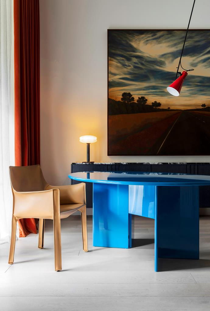 A festival of colour brings the study to life and is centred around a glossy blue Cassina 'Antella' table from Castorina & Co, which was originally designed in the 1970s by Kazuhide Takahama for SimonCollezione. Cassina 'Cab' chair by Mario Bellini and Astep 'VV Cinquanta' suspension light by Vittoriano Viganò from Mobilia. A 'Fenice' table lamp by Stefano Marcato on the custom-designed credenza by Kerry Phelan. *There is time for you to find me* artwork by Jason Benjamin.