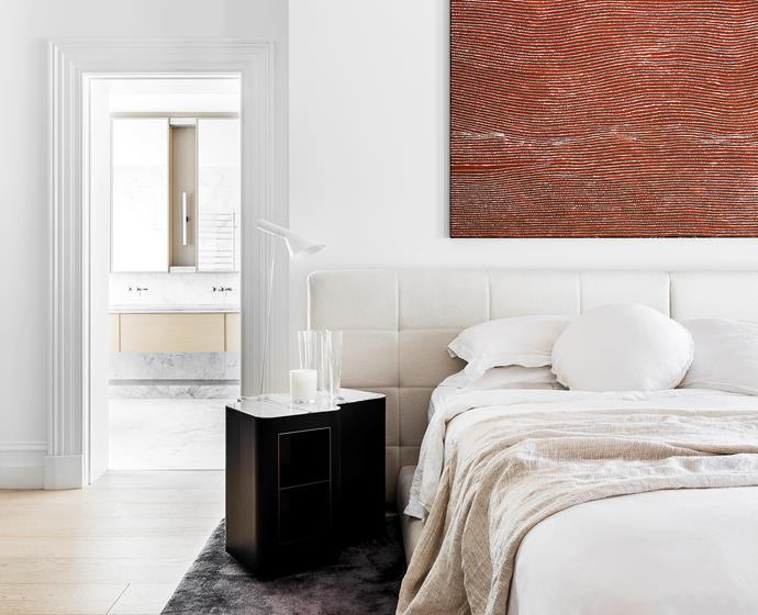 """We find it very soothing to be surrounded by Aboriginal artworks,"" says the owner, referring to the painting by Willy Tjungurrayi in the master bedroom. ""There's an earthy energy and power in these works."" Custom bed designed by Kerry Phelan. Minotti nightstand by Christophe Delcourt and rug by Rodolfo Dordoni, both from De De Ce. Louis Poulsen lamp from Cult."