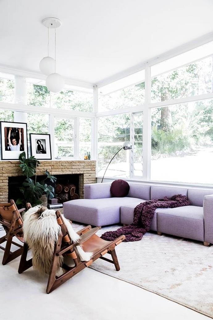 Lilac, plum and buttery leather arm chairs combine to create a cosy vibe in this light-filled living room that has been styled for the cooler months.