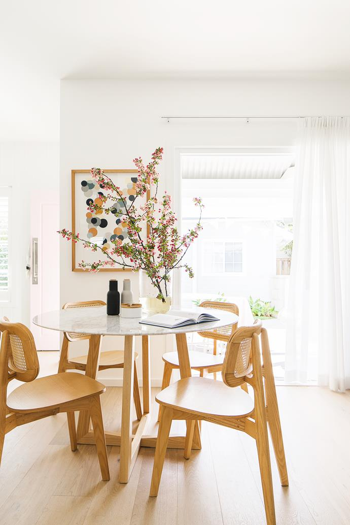 """The north-facing home is blessed with gorgeous incoming sun, and Merrilyn and Simone capitalised on that with smart light-enhancing surfaces: walls in Dulux Vivid White and Woodcut engineered European oak flooring in Voss. Beyond the home's bones though, it's the little touches that bring panache, such as the pretty-in- pink front door, painted Dulux Soft Satin, and the bunch of pussy willow on the Trit House marble dining table (joined by cane chairs, also from Trit House). """"A woman at the local market does beautiful native flowers – I always get some when guests are coming,"""" says Merrilyn. The 'Rust Confetti' artwork by Rachel Castle reflects the room's warm palette."""