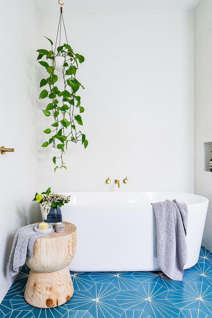 """""""The wood gets a bit marked by water, but we don't mind,"""" says Simone. """"It makes the space feel less stark."""" And there's the freestanding Caroma tub; this wall originally housed laundry appliances, but they were relocated to the garage to give priority to a sumptuous soak."""