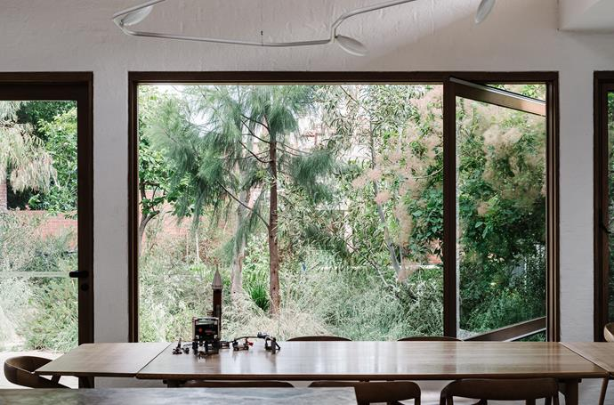 Trees and foliage grow right up to the window, ensuring a strong indoor-outdoor connection.