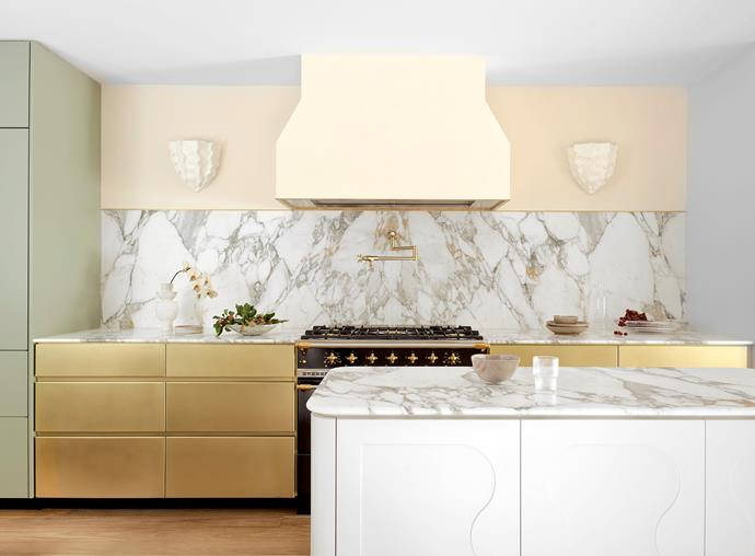 The kitchen has a glamorous look with brass drawer fronts, and benchtops and splashback in Arabescato Vagli marble. Plaster wall sconces by Aerin. Brodware tapware. The scallop motif is repeated in relief on the kitchen island which is painted in Resene 'Athens Grey'.