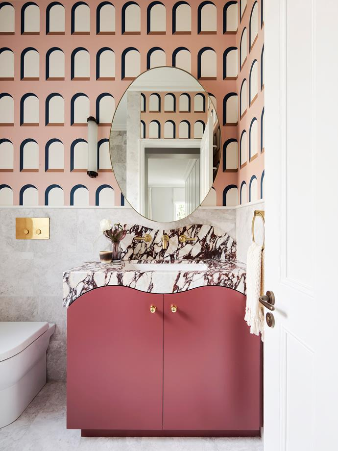 The ensuite walls are covered in Sandberg 'Marie' wallpaper in Pink and Oriana marble. The custom cabinetry by Arent&Pyke is in Dulux 'Loganberry' with a Calacatta Viola marble top. Brodware tapware. 'Cabin' wall sconce from Dunlin.