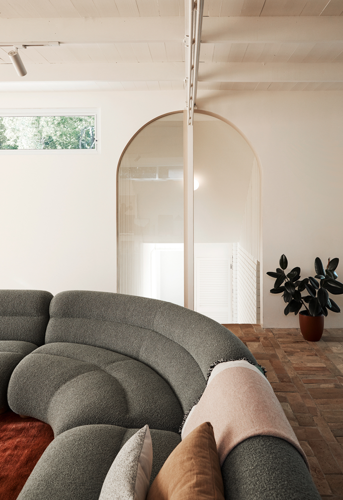 "The addition of curves and arches helps this family home feel less formal. ""It was really important to the owners that the house was fun to live in,"" says Cushla McFadden, director of Tom Mark Henry creative studio. The curved modular Valley sofa from Jardan is adorned with Hay cushions and a Hay throw."