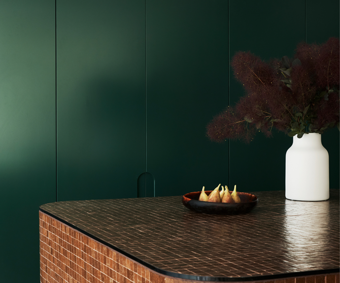 The designers used shades of green and brown throughout the house to echo the environment outside. Custom joinery in the kitchen is painted Dulux 'Deep Mooring' and the custom island is tiled with Vixel glass mosaic tiles from Artedomus.