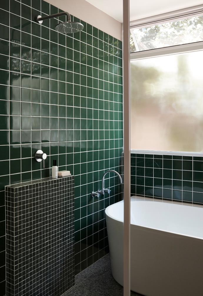 A large pane of frosted glass in the main bathroom throws light against a wall of emerald green glazed porcelain tiles from Surface Gallery.