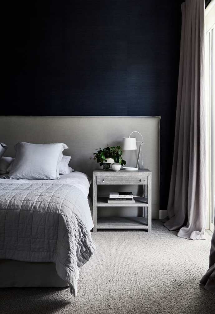 Dark and moody tones invite deep relaxation in Diana and Tom's domain. Juxtaposed against a wall clad in Porter's Paints 'Navy' Grasscloth wallpaper, a bespoke bedhead by Peoni Home is teamed with a bed dressed in Abbotson linen from Sheridan.