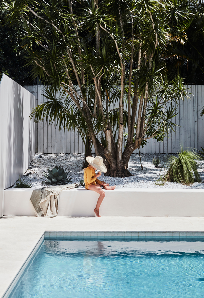 Large-format travertine pavers have been paired with natural marble waterline tiles in this pool belonging to interior stylist Kristin Rawson. Her seven-year-old daughter Billie wears swimmers from Yoli & Otis. Beach blanket from Land & Sand Essentials.