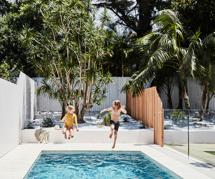 Kristin's children Billie, 7, and Jackson, 9, delight in their newly upgraded backyard. Kristin added two styles of silver ash fencing, installed by Screening Solutions in Melbourne. The pool equipment is concealed by batten fencing that integrates into the drop edge of the pool, meeting up with the glass pool fence. The beach blanket is from Land & Sand Essentials.