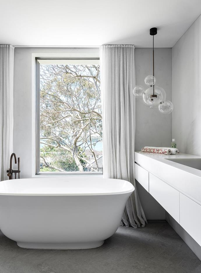"""Display towels and toiletries create a hotel-style bathroom at home. Light, texture and scene-stealing vistas set a postcard-perfect scene in this [stunning Sydney family home](https://www.homestolove.com.au/california-bungalow-transformed-into-a-contemporary-coastal-home-22298 target=""""_blank"""")."""