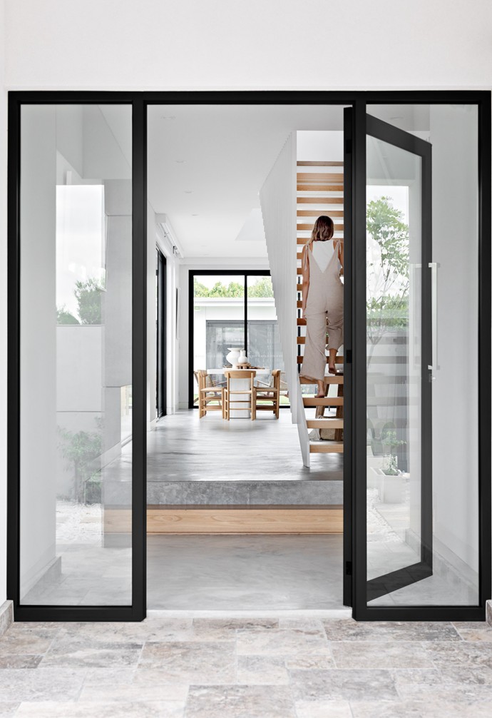 """The open plan entryway is framed with [steel glass black doors](https://www.homestolove.com.au/steel-frame-doors-20439