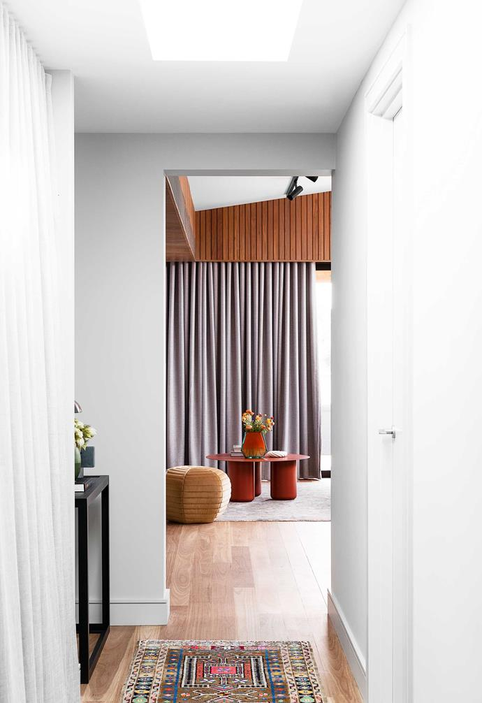 """**Hallway** Looking into the living area, where the tops of the curtains and air-conditioners are concealed by the batten detail encircling the space. """"Putting timber up there makes it feel much more special,"""" says Alexandra. """"It also draws the eye up to the detail of the roof."""" Flooring, natural blackbutt with a matt finish. Rugs throughout the home, [Cadrys](https://www.cadrys.com.au/