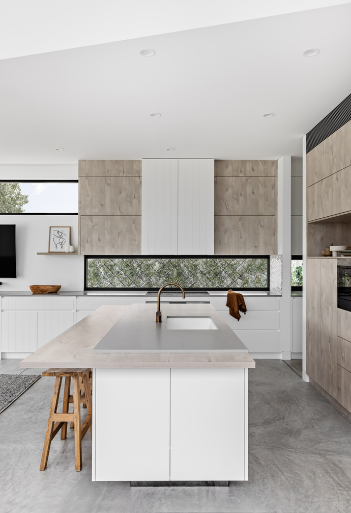 The kitchen design features a two-tone island bench, which pairs perfectly with a custom natural cabinetry colour and minimalist finish selections.