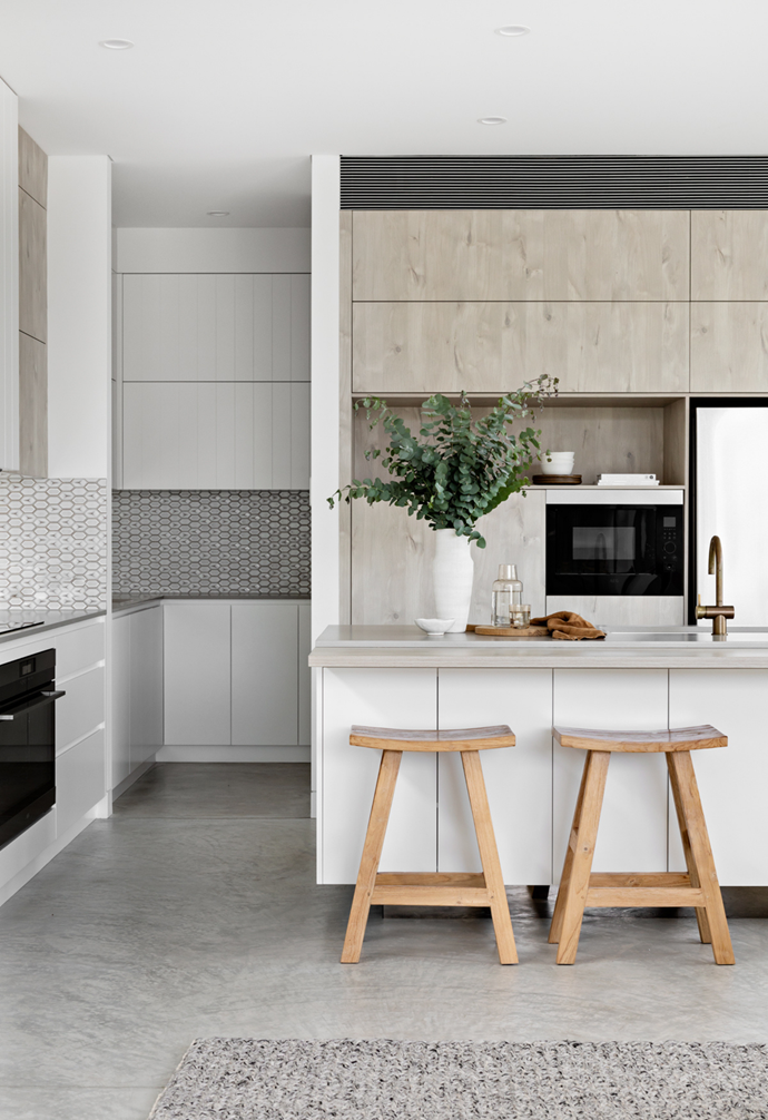 Luxury kitchen featuring warm, washed tones throughout cabinetry. Timber stools contrast the light base of the space. Feature splashback tiles tie all textures together and carry through to hidden butler's pantry.