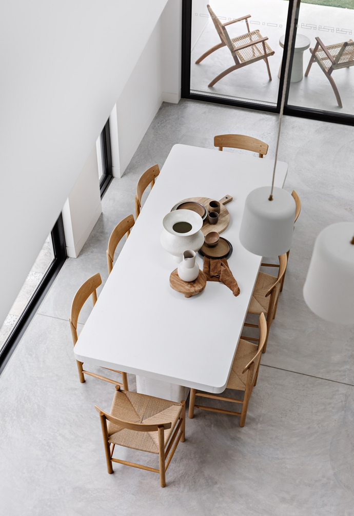 Shot of dining space through architectural void of modern dining table, styled pendant lighting overhanging. Subtle whites and greys wash Santorini into the space.