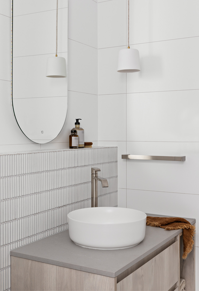 The powder room's vanity and countertop vessel basin continue the main bathroom's them of with finger tiles and a neutral palette. A white pendant light, tapware choices and ledge wall add further functionality to the space.