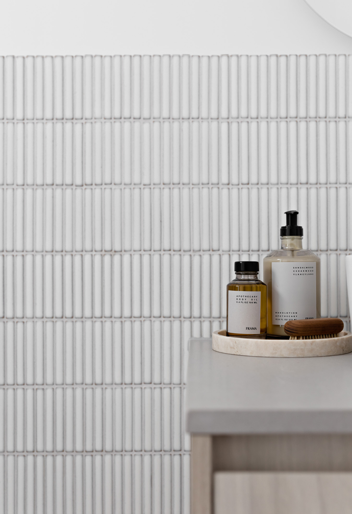 Intricate white mosaic bathroom tiles are the hero in the powder room, layered against a delicate joinery veneer and benchtop.