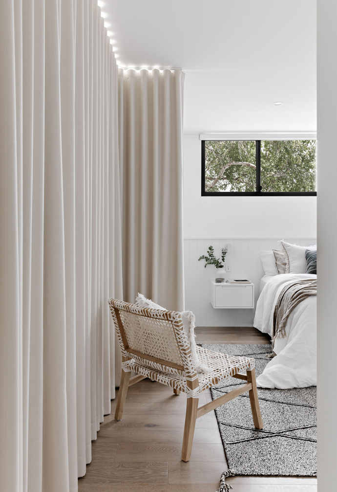 The main bedroom is complete with floor to ceiling curtains, and a rattan occasional chair. Fabric colours and textures give a light & natural feel to the room.
