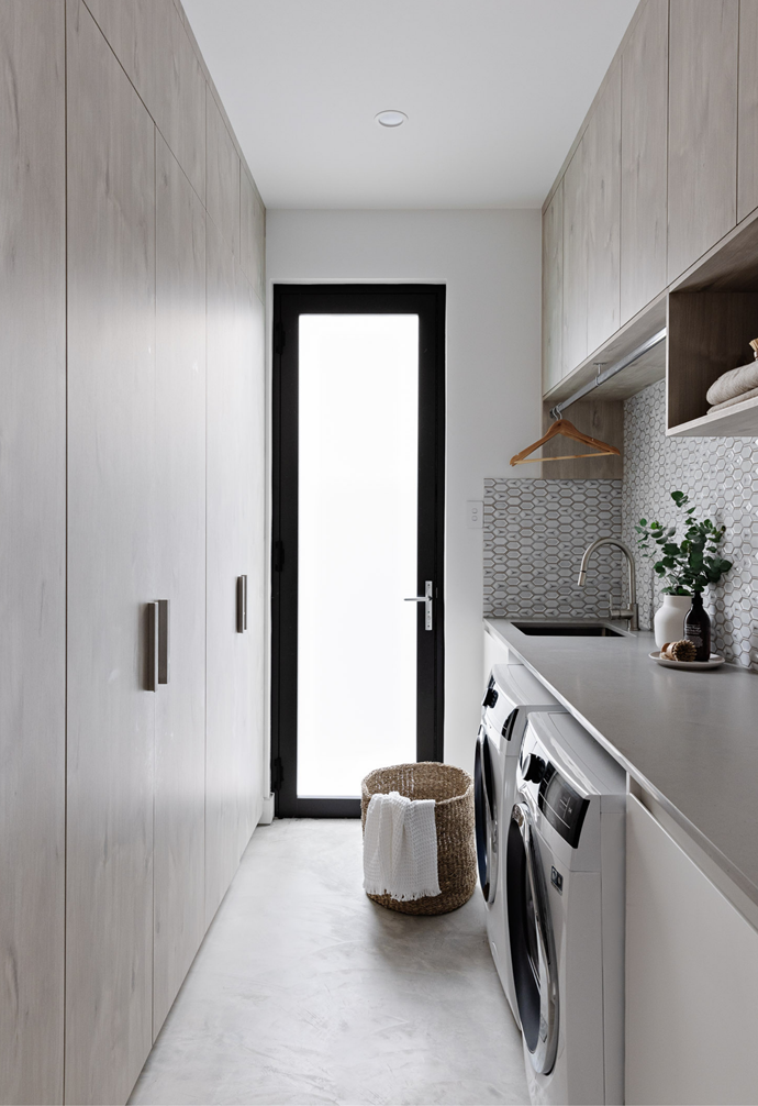 A luxury internal laundry with hexagonal mosaic splash back tiles is fitted with custom joinery design for increased family functionality. A black framed door with frosted glass provides external access.