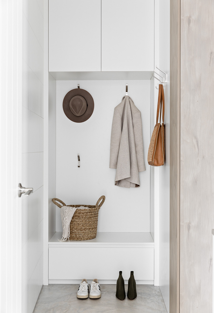 The modern mudroom features custom joinery design for family functionality, including storage hooks for versatile use and extra storage.