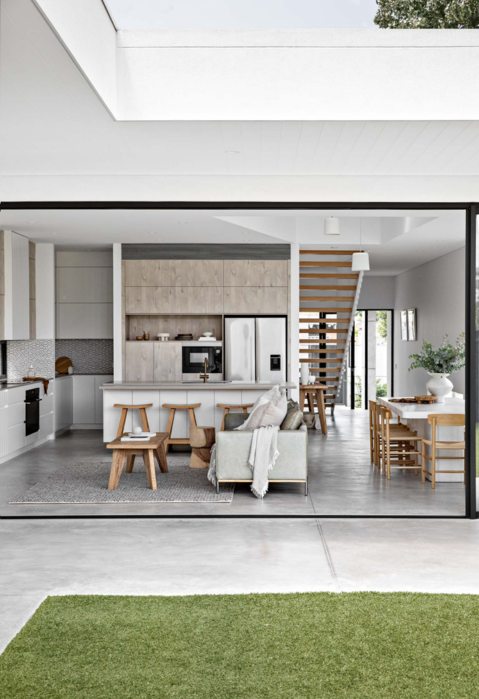The home's open plan living, kitchen, dining and alfresco spaces flow out to an alfresco entertaining area and garden. Black framed glass doors provide contrast against a white architectural base in both the interior and exterior designs.