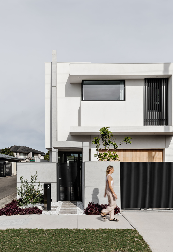 The front façade and entryway are in mainly monochrome tones. Landscaping selections reflect the whites and greenery of Santorini in the pebbling, olive trees and shrubbery.