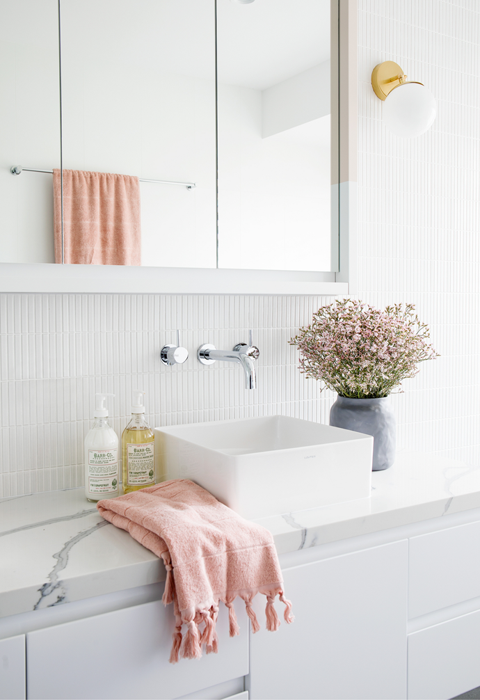 At first, Steve and Victoria's ensuite wasn't on their hit-list, but once the renovation ball was rolling, they realised it too would need a cosmetic upgrade. Sticking to the same layout, they switched fixtures to a neutral, timeless scheme featuring large-format Anthracite floor tiles from Stone And Tile Studio and beautifully slender Yohen Border YB1 tiles from Artedomus on the vanity wall. Below the window, a Reece Kado 'Lussi' cast bath makes a wonderful spot to unwind and the Vitra cork stool from Living Edge ensures toiletries are in reach. A 'Line' wall light in Brass with a brushed and lacquered finish, is from Douglas & Bec.